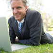 Businessman with laptop lying in park — Stock Photo #42938091