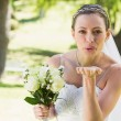 Bride with bouquet blowing kiss — Stock Photo