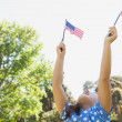Girl holding up two American flags at park — Stock Photo