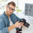 Handsome photographer holding his camera smiling — Stock Photo #42938491