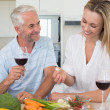 Cheerful couple making dinner together and drinking red wine — Stock Photo