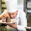 Concentrated male pastry chef decorating dessert in kitchen — Stock Photo #42938709