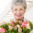 Retired woman holding bouquet of flowers smiling at camera — Stock Photo #42938915