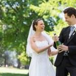 Newlywed couple opening champagne bottle — Stock Photo #42938979