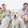 Happy family sitting on couch with their pet labrador — Stock Photo #42938981