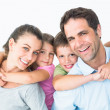 Smiling young family looking at camera together — Stock Photo #42939047