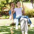 Happy mother and daughter sitting on swing at park — Stock Photo #42939145