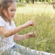 Relaxed young girl sitting in field — Stock Photo #42939225