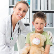 Friendly doctor with boy holding teddy bear — Stock Photo #42939243