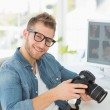 Photographer holding his camera and smiling — Stock Photo #42939321