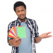 Portrait of a confused man holding colorful papers — Stock Photo #42939423
