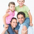 Parents giving their children piggyback ride smiling at camera — Stock Photo