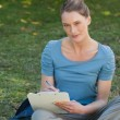 Relaxed young woman writing on clipboard at park — Stock Photo #42939827