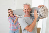 Happy couple carrying a rolled up rug together — Stock Photo