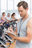 Trainer with people working out at spinning class — Stock Photo
