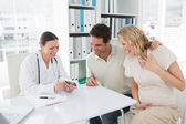 Gynaecologist and expectant couple — Stock Photo