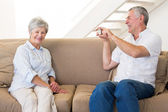Retired man taking photo of his partner on the couch — Stock Photo