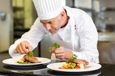 Concentrated male chef garnishing food in kitchen — Stock Photo