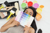 Woman with paint samples and paintbrush — Stock Photo