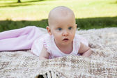 Cute baby lying on blanket at park — Stock Photo