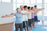Class stretching hands in row at yoga class — Stock Photo