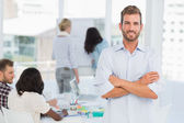Handsome man smiling at camera while his colleagues are working — Stock Photo