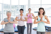Class standing in namaste pose at yoga class — Stock Photo