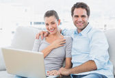 Happy couple sitting on the couch using laptop together — Stock Photo
