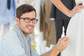 Male fashion designer adjusting dress on model — Stock Photo
