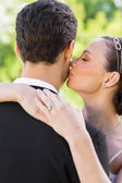 Bride kissing groom on cheek — Stock Photo