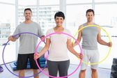 Fitness class holding hula hoops in gym — Stock Photo