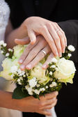 Newlywed couple with wedding rings and bouquet — ストック写真