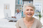 Happy senior patient with doctor at medical office — Stock Photo
