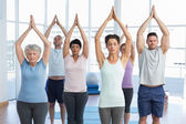 People with eyes closed and joined hands at fitness studio — Stock Photo