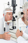 Optometrist doing sight testing for senior patient — Foto Stock