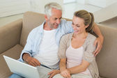 Happy couple using the laptop together on the couch — Stock Photo