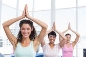 Sporty women with joined hands over head at fitness studio — Stock Photo