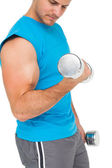 Mid section of a fit young man exercising with dumbbells — Photo