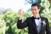 Groom toasting champagne flute — Stock Photo