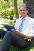 Businessman with digital tablet in park — Stock Photo