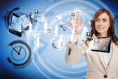 Businesswoman pointing to apps flying between devices — 图库照片