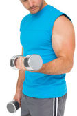 Mid section of a fit man exercising with dumbbells — Stock Photo