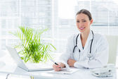 Doctor at desk in clinic — Stock Photo