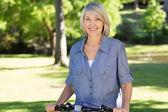 Mulher com bicicleta no parque — Foto Stock