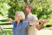Couple arms outstretched in park — Stockfoto