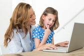 Mother teaching daughter to use laptop — Stock Photo