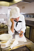 Cook using cellphone in kitchen — Stock Photo