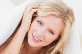 Blonde smiling from under the duvet — Stock Photo
