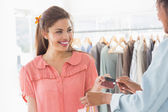 Customer receiving credit card from saleswoman — Stock Photo