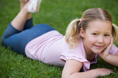 Smiling relaxed girl lying on grass at park — Stock Photo